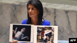 U.S. Ambassador to the UN Nikki Haley holds photos of victims of the Syrian gas attack as she speaks as the UN Security Council meets in an emergency session in New York last week.