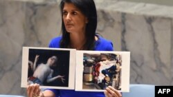 U.S. Ambassador to the UN Nikki Haley holds up photos of victims as she speaks as the UN Security Council in an emergency session on April 5 to discuss the apparent chemical-gas attack in Syria.