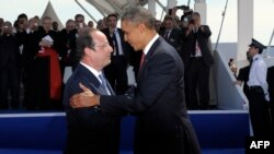 U.S. President Barack Obama (right) talks with French President Francois Hollande during the international D-Day commemoration ceremony in Normandy on June 6.