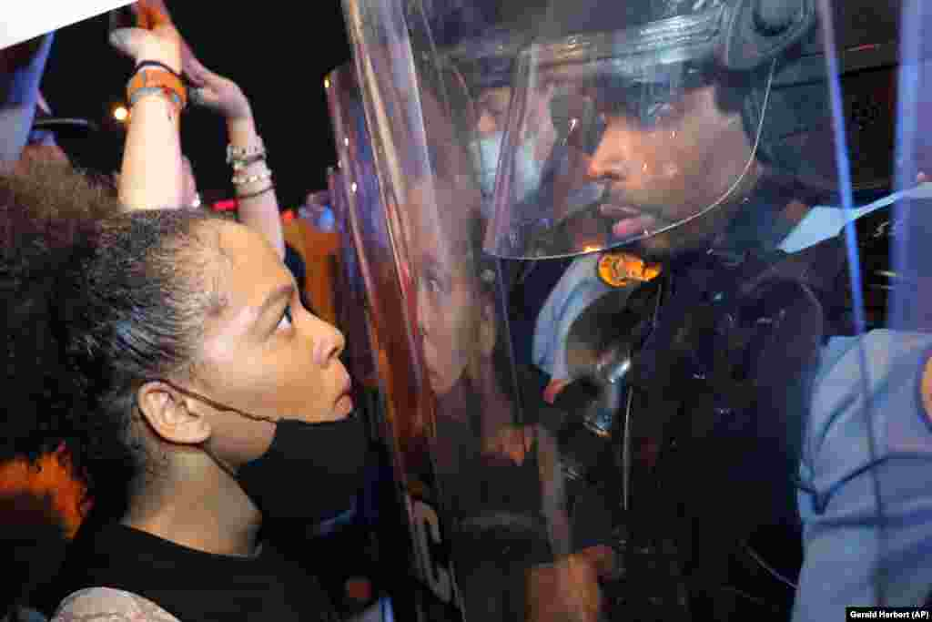 Протестувальниця та поліцейський віч-на-віч на мостіCrescent City Connection, який пролягає через річкуМіссісіпі в Новому Орлеані, під час протесту, пов'язаному зі смертю Джорджа Флойда. Новий Орлеан, штат Луїзіана, 3 травня 2020 року(Фото AP/Gerald Herbert)