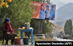 A woman sells fruit on the side of a road in front of a campaign billboard for the Bir Bol (Stay Together) party in the village of Koy-Tash, some 20 kilometers from the capital, Bishkek, on September 30.