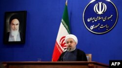 Iranian President Hassan Rohani delivers a speech next to a portrait of the founder of Iran's Islamic republic, Ayatollah Ruhollah Khomeini, during a press conference in Tehran last month.