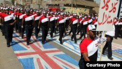 Supporters of Muqtada al-Sadr march in the street and trample on the Israeli, British, and U.S. flags in Baghdad in May.