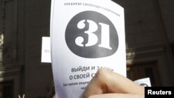 "An opposition supporter holds up a leaflet with the number ""31"" on it during a rally in Moscow on May 31."