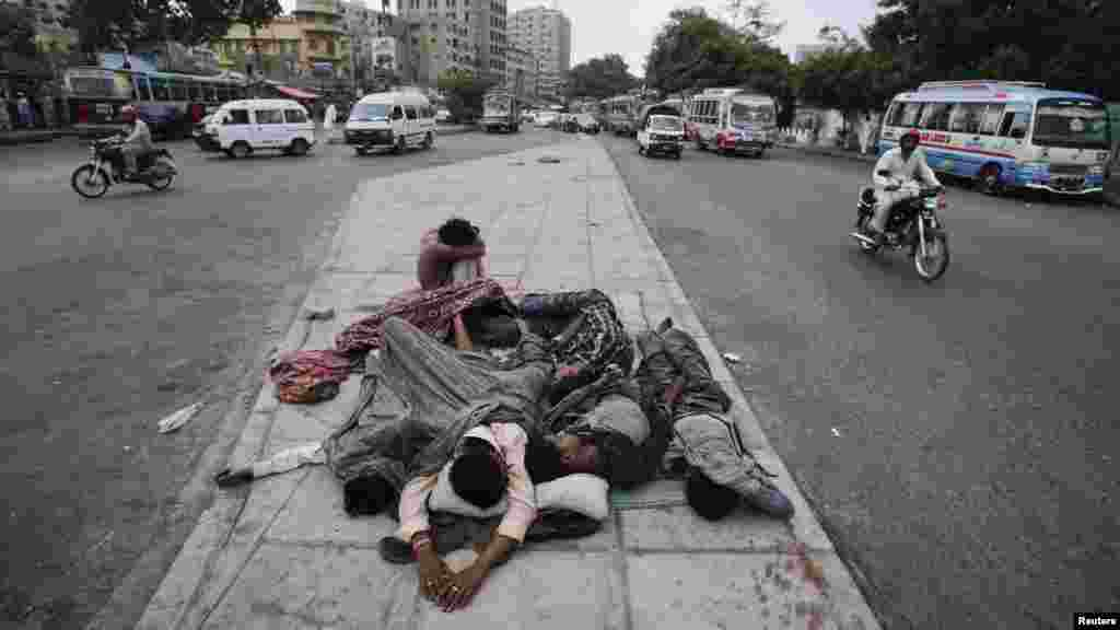 Pakistani youths sleep on a road median early in the morning in Karachi on August 1. (REUTERS/Akhtar Soomro)