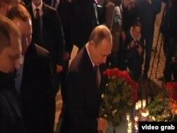 Президент России Владимир Путин возлагает цветы у стихийного мемориала после теракта в Санкт-Петербурге. 3 апреля 2017 года.