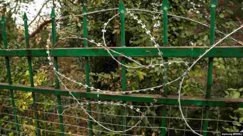 Залізний паркан з «єгозою» на ньому, за яким розташовані занедбані літні будиночки в центральній частині Плаки