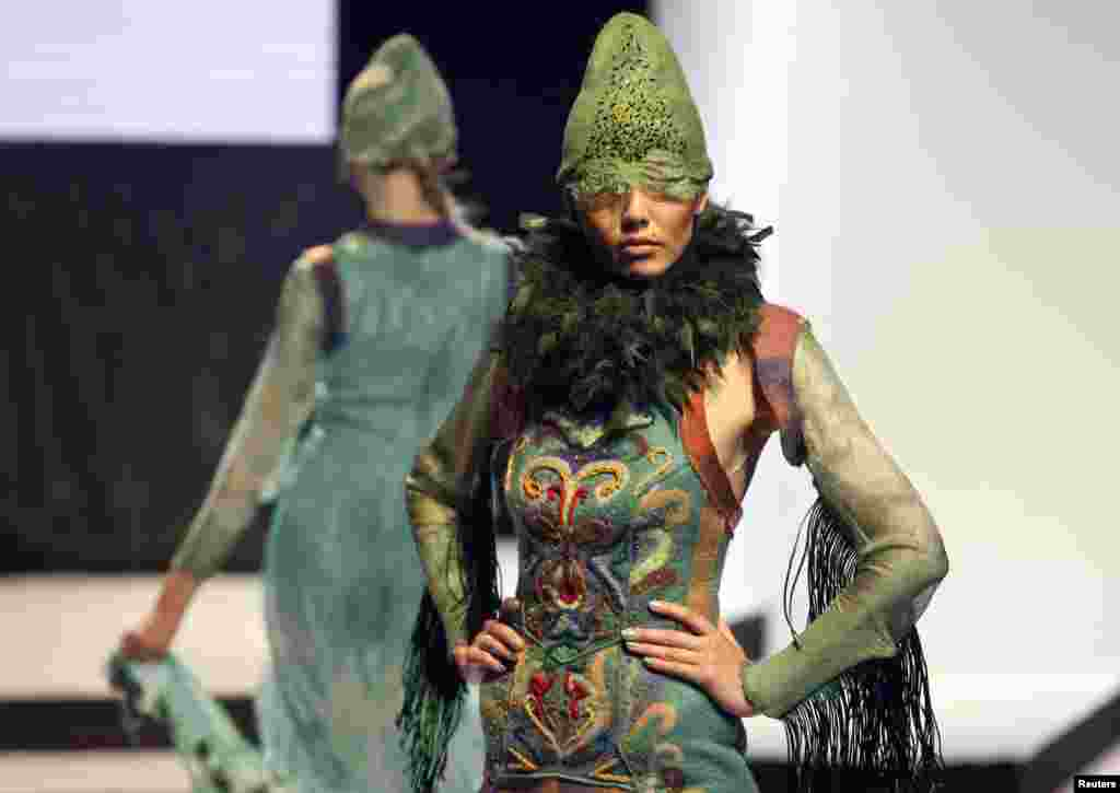 Models present creations by designer Talshyn Kokenova during the OPEN WAY National Contest of Young Designers in Almaty on September 27, 2012.