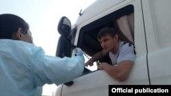Медик измеряет температуру тела водителя грузовой машины. Иллюстративное фото.