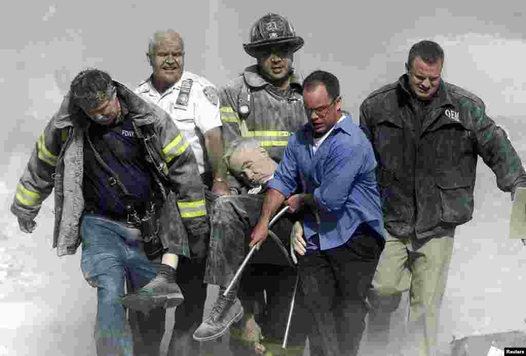 Паліцыянт, пажарнікі і цывільная асоба нясуць цела капэляна Нью-ёрскай пажарнай службы Майкла Джаджа, які загінуў пры разбурэньні паўднёвай вежы Ўсясьветнага гандлёвага цэнтру, 11 верасьня 2001 году.