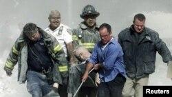 رجال إنقاذ وشرطة أميركيون يحملون رجلاً قضى في إنهيار برجي مركز التجارة العالمي بنيويورك