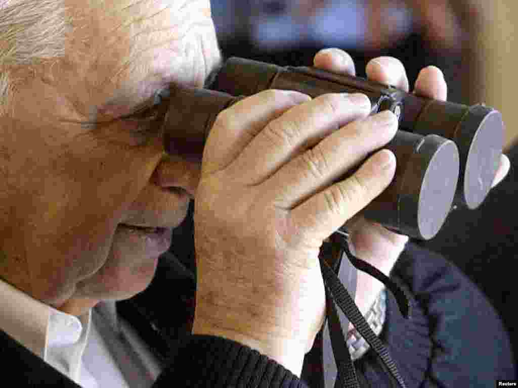 Israel - Israeli Prime Minister Ariel Sharon tries to look through binoculars which still have their lenses caps on near Tel Aviv, January 7, 2003. REUTERS