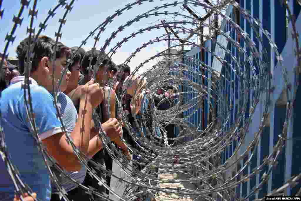 Youths from a camp for the displaced in the Syrian village of Al-Rafid clutch a barbed-wire fence near a checkpoint along the border with the Israeli-annexed Golan Heights during a protest against the Syrian government and calling for international protection. (AFP/Jawad Abu Hamza)