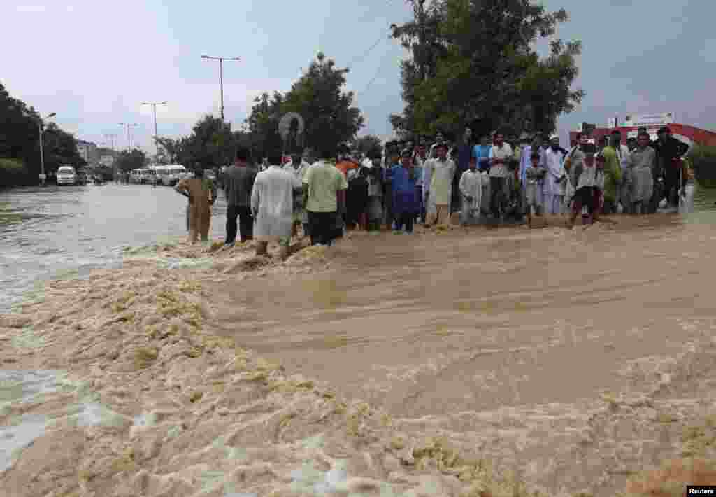 Residents wait to cross a flooded road outside of Karachi on August 4.