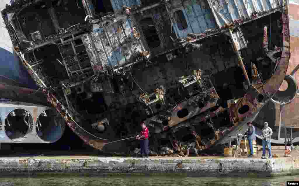 Men fish in front of wrecked ships at the Russian fleet base in Baltiysk in the Kaliningrad region. (Reuters/Maxim Shemetov)