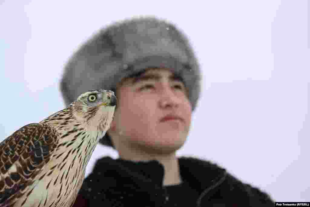 Ловец с ловна птица на на рамото наблюдава състезанието.