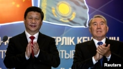 Kazakh President Nursultan Nazarbaev (right) and his Chinese counterpart Xi Jinping applaud after a gas pipeline launch.