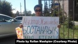 Гражданская активистка Толкын Шауалиева с плакатом «Мұхтар Жәкішевке бостандық талап етемін!» («Я требую освободить Мухтара Джакишева!») у здания суда № 2 города Семея. Семей, 7 августа 2019 года.