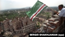 A man waving a separatist Chechen flag in Grozny, the region's capital, in 1995. Many buildings were destroyed by Russian bombs and other weaponry in the 1994-96 war between federal troops and Chechen rebels, which ended with de facto independence for Chechnya.