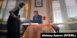 Балалар үйі директоры кабинетінде отыр. «Үзілмеген үміт» фильмінен алынған кадр.