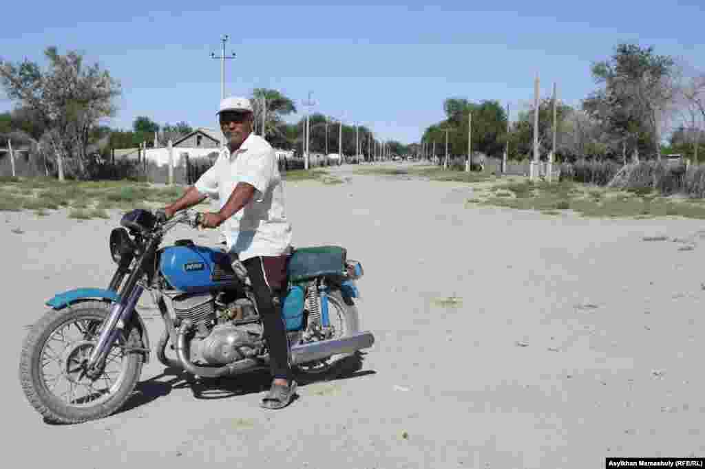 Мотоцикль мінген ауыл тұрғыны.