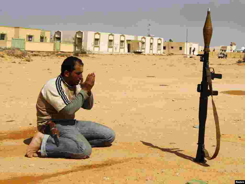 A rebel fighter prays along a road in Wadi Al-Hamra on March 28. Photo by Youssef Boudlal for Reuters