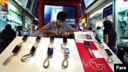 A shopkeeper adjusts mobile-phone handsets at a shopping center in Tehran. (file photo)