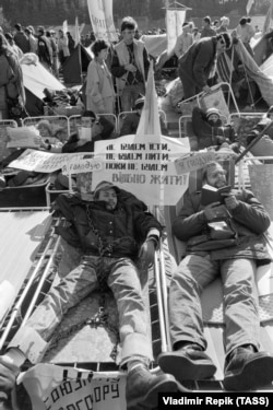 """A student hunger striker wearing symbolic shackles. The sign reads: """"We won't eat, we won't drink until we will live freely."""""""
