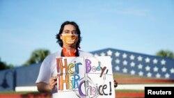 """Cesar Rios, 24 vjeç, një mbështetës i të drejtës së abortit mban një pankartë ku shkruhet """"Trupi i tyre, zgjedhja e tyre""""."""