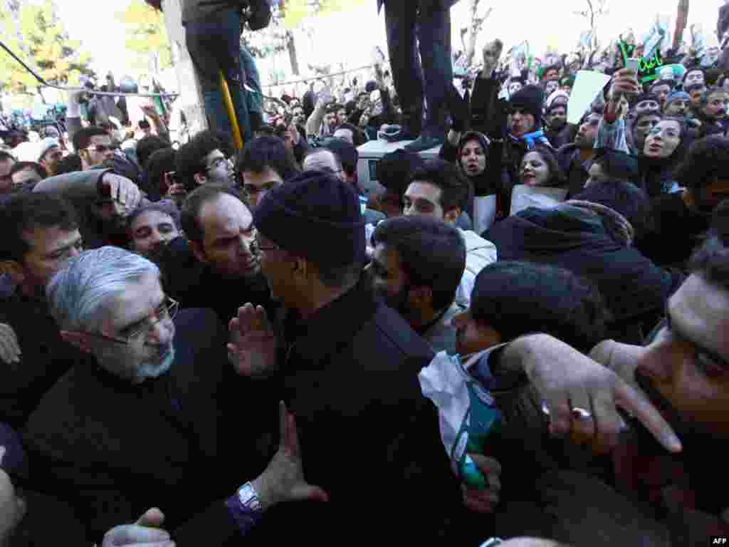 Iranian opposition leader Mir Hossein Musavi (left) attends the procession, surrounded by security.