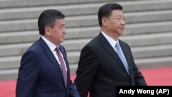 Kyrgyz President Sooronbai Jeenbekov (left) walks with Chinese President Xi Jinping during a welcome ceremony outside the Great Hall of the People in Beijing on June 6.