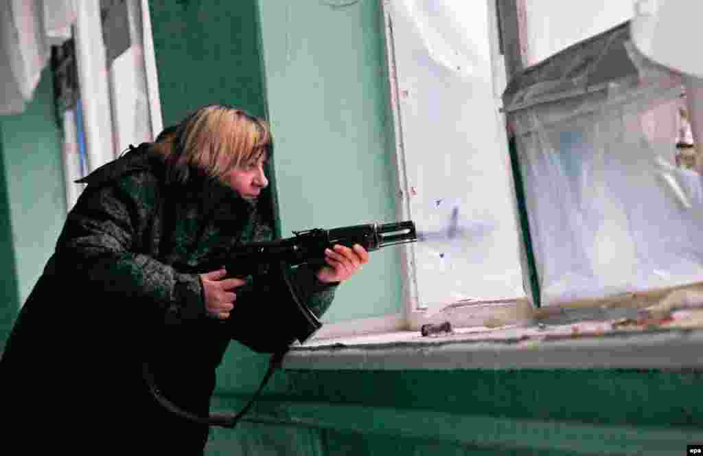 An armed pro-Russia militant holds her position inside a damaged school in the village of Zaytseve in the Donetsk region. (epa/Alexander Ermochenko)