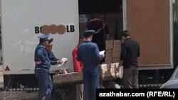 Turkman politsiyachilari oziq-ovqat olib ketayotgan avtomashinani tekshirmoqda.