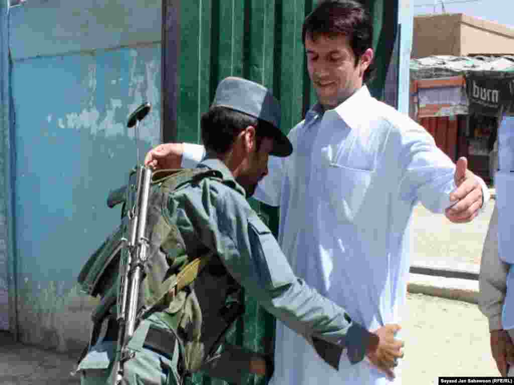 A police officer searches a voter entering a polling station in the Afghan capital.