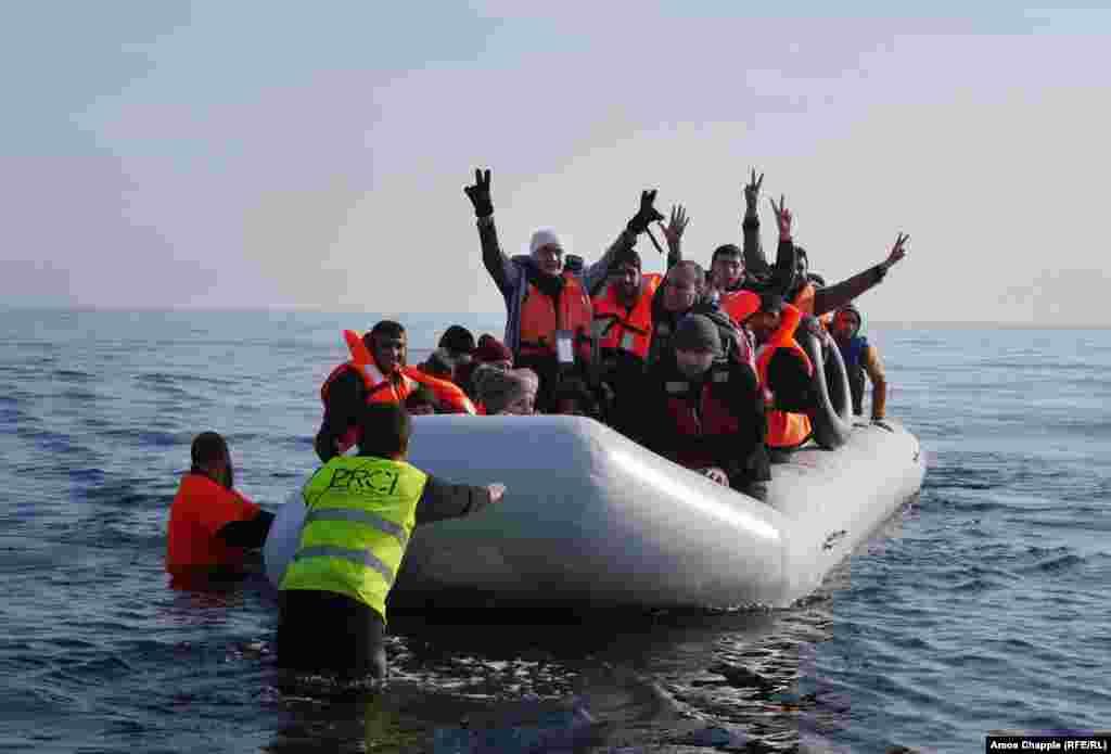 Бежавший из Сирии Дауд Дауд (в центре лодки) поднял руки, когда надувная лодка, в которой он плыл вместе с другими мигрантами, приблизилась к побережью Лесбоса.
