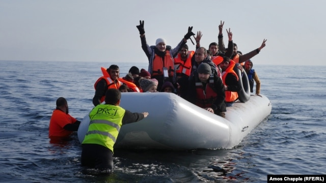 Syrian student Daoud Daoud (center, arms raised) was one of 4,000 new arrivals to the island of Lesbos during the last weekend in February.