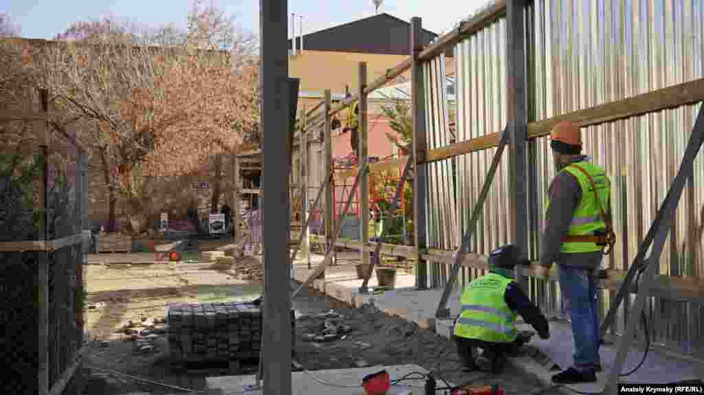 Будівельники монтують паркан довкола старого лялькового театру