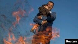 От жагып, баласын жылытып жаткан мигрант. Венгрия. 8-сентябрь, 2015-жыл