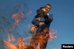 Біженець з дитиною гріються біля вогню на угорсько-сербському кордоні