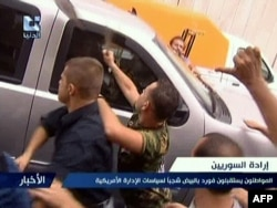A TV video grab shows pro-regime supporters attacking a U.S. Embassy vehicle in Damascus on September 29.