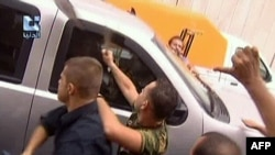 A TV grab shows pro-regime supporters attacking a U.S. embassy vehicle in Damascus in September 2011.