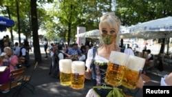 Официант несет кружки пива во время знаменитого пивного фестиваля Октоберфест в Мюнхене. Германия, 19 сентября 2020 года.