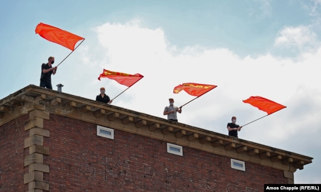 MLPD supporters wave flags featuring the communist hammer and sickle, while crowds sing the Internationale, the socialist anthem, moments after the Lenin monument was uncovered.