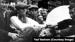In an undated photo taken during World War II, a Jewish man in western Ukraine is attacked by a mob next to a bust of Lenin.
