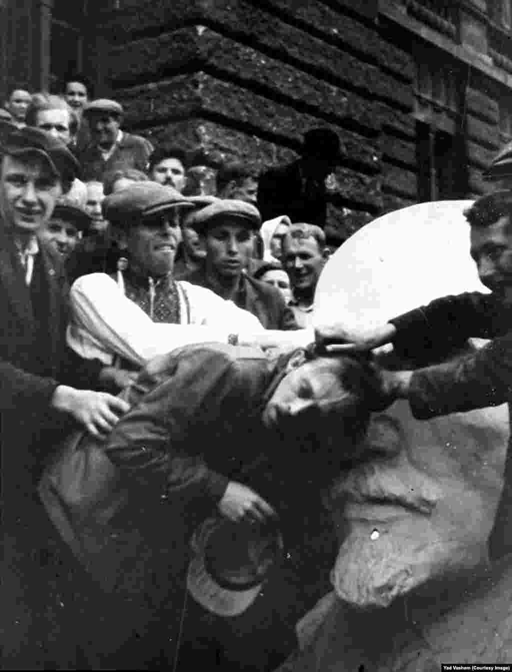 A Jewish man in western Ukraine being attacked by a mob next to a bust of Lenin. After occupying Nazi forces opened Soviet secret police prisons, atrocities carried out under Stalin were laid bare and exploited by Nazi propagandists, who fueled anti-Semitism by highlighting the Jewish backgrounds of some early Soviet leaders.