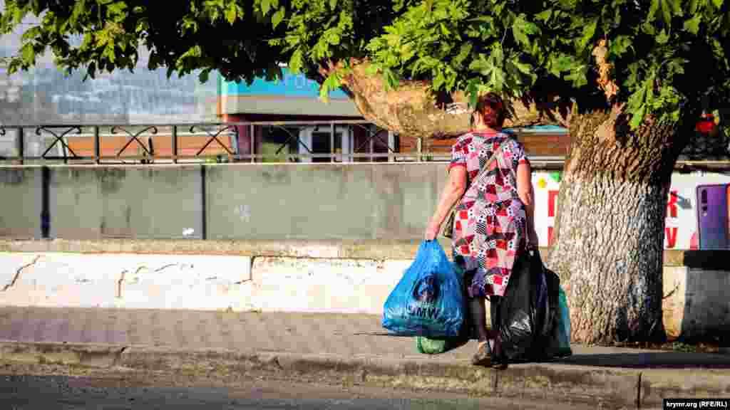 Женщина с пакетами зелени направляется в сторону остановки