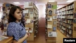 Співробітниця Бібліотеки української літератури стоїть біля книжкових полиць. Москва, 29 жовтня 2015 року
