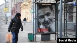 Плакат на автобусній зупинці у Москві з зображенням Надії Савченко і написом «Live! Живи!» 8 березня 2016 року