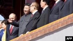 Президент Китая Си Цзиньпин (третий слева) беседует с бывшим президентом Китая Цзянь Цзэминем (четвертый слева) во время парада в Пекине, 3 сентября 2015 года.