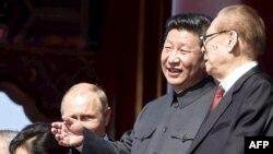 Қытай президенті Си Цзиньпин (ортада) елдің бұрынғы президенті Цзянь Цзэминмен (оң жақта) сөйлесіп тұр. Пекин, 3 қыркүйек 2015 жыл.